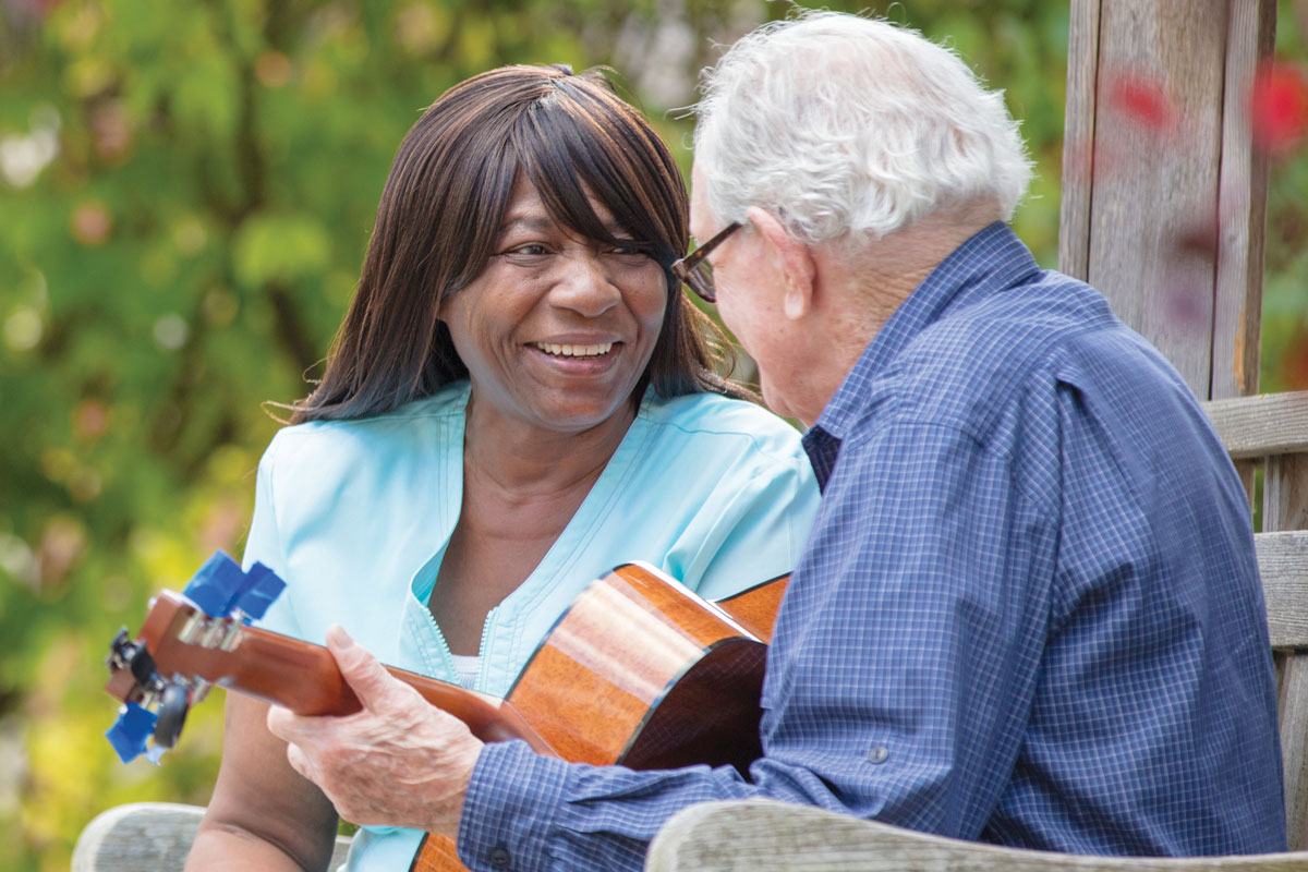 senior man plays guitar for a woman