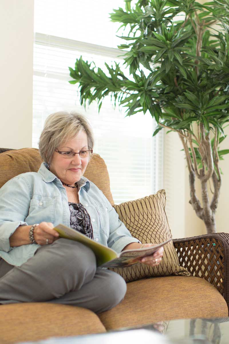 senior woman sitting on a couch reading a magazine