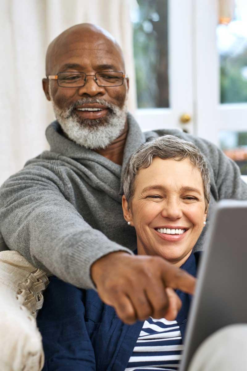 senior couple looking at ipad